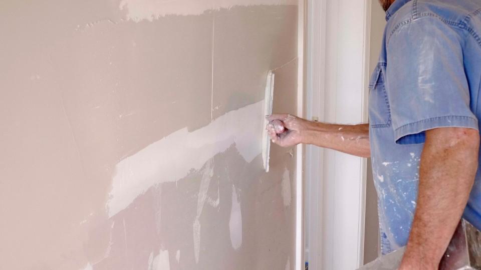 person applying drywall mud